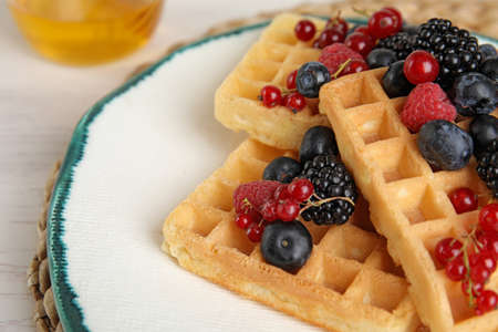 Delicious waffles with fresh berries served on white wooden table, closeup