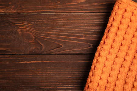Orange kitchen towel on wooden background, top view. Space for text Banco de Imagens