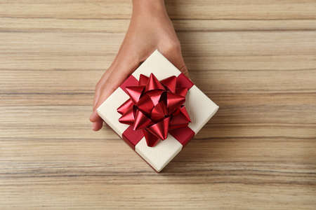 Woman holding beautiful gift box over wooden table, top view Stock Photo