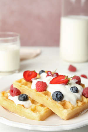 Delicious waffles with fresh berries served on white wooden table against pink background