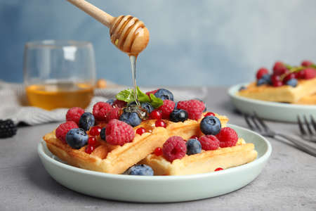 Pouring honey onto delicious waffles with fresh berries served on grey table 스톡 콘텐츠