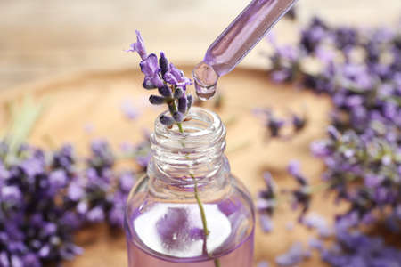 Natural oil dripping into bottle and lavender flowers on table, closeup. Cosmetic product