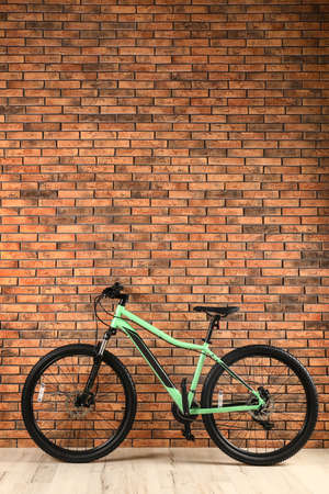 Modern bicycle near brick wall indoors. Space for text
