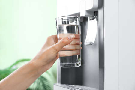 Woman filling glass from water cooler indoors, closeup. Refreshing drink Stock Photo