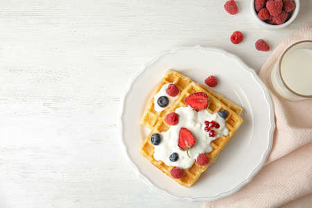 Flat lay composition with delicious waffles and fresh berries on white wooden table. Space for text 스톡 콘텐츠