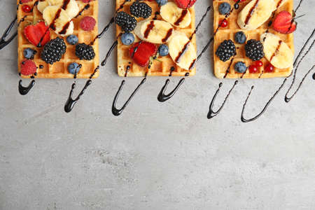 Flat lay composition with delicious waffles and fresh berries on grey table. Space for text