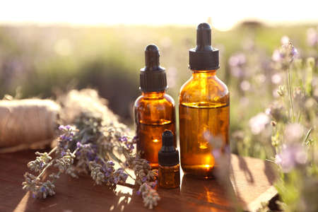 Bottles of lavender essential oil on wooden table in field