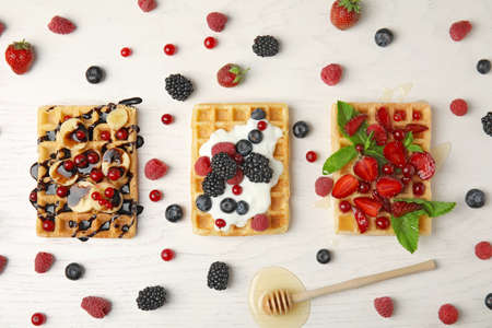 Flat lay composition with delicious waffles and fresh berries on white wooden background