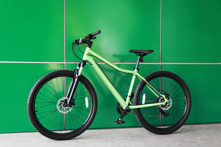 New modern color bicycle near green wall outdoors 写真素材