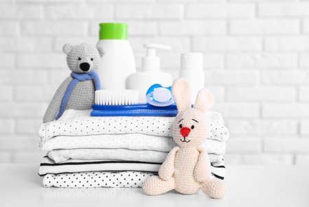 Baby accessories on table near white brick wall