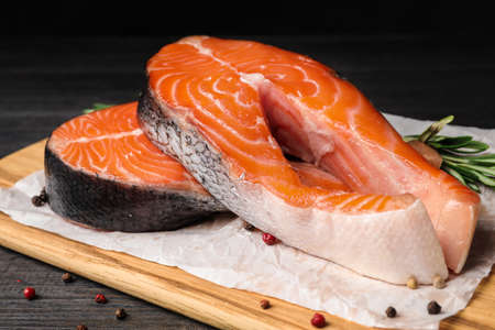 Fresh salmon steaks with spices on black wooden table Stockfoto