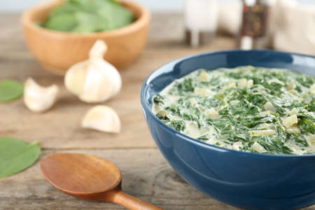 Tasty spinach dip in bowl on wooden table