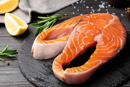 Fresh salmon steaks on black wooden table