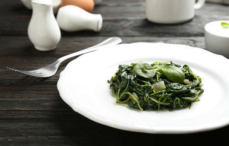Plate with tasty cooked spinach on black wooden table, closeup. Healthy food