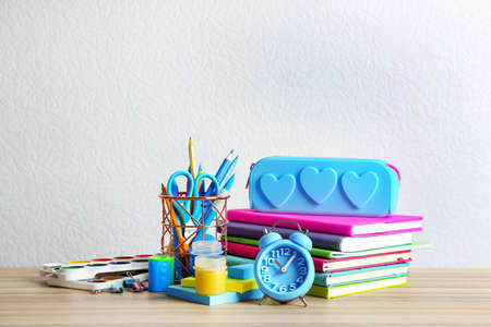 Different school stationery on wooden table against white background