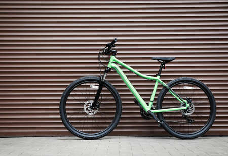 New modern color bicycle near brown wall outdoors
