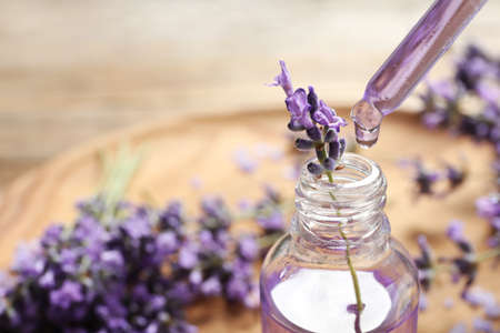 Natural oil dripping into bottle and lavender flowers on table, closeup with space for text. Cosmetic product