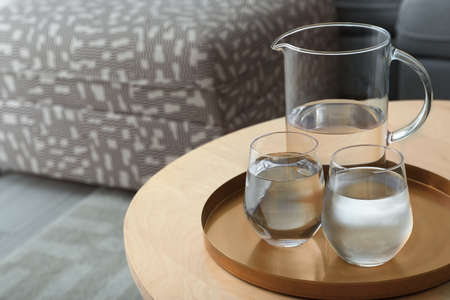 Tray with jug and glasses of water on wooden table in room, space for text. Refreshing drink