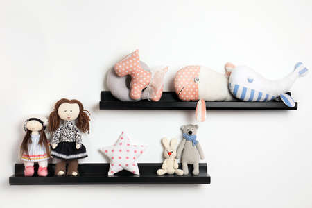 Different stuffed toys on shelves in child room Archivio Fotografico