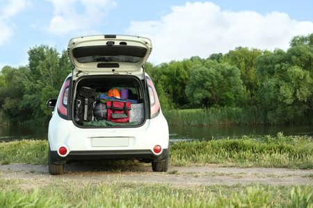 川岸のトランクにキャンプ用品を備えた車。テキスト用のスペース