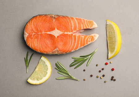Flat lay composition with salmon steak on grey background