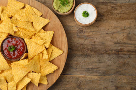 Mexican nacho chips with different sauces on wooden background, flat lay. Space for text