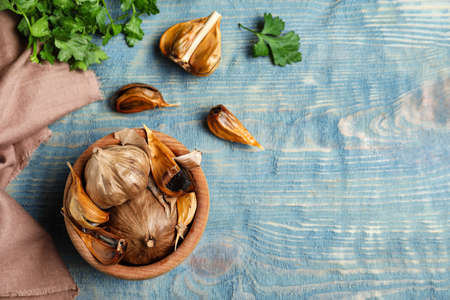 Flat lay composition with bowl of black garlic on blue wooden table. Space for text