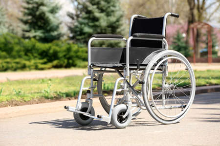 Empty wheelchair in city park on sunny day