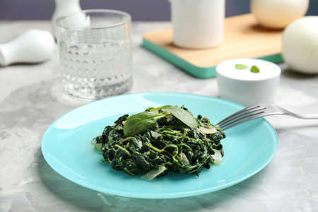 Tasty cooked spinach and fork on grey table. Healthy food