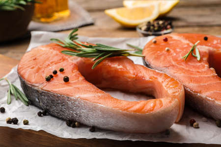 Fresh salmon steaks with spices and rosemary on table, closeup view