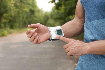 Joven comprobando el pulso con un dispositivo médico después del entrenamiento en el parque, primer plano