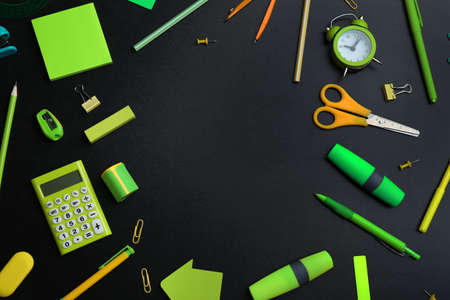 Frame of different bright school stationery on black background, flat lay. Space for text