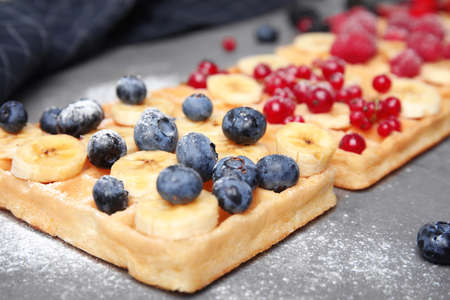 Delicious waffles with fresh berries served on grey table, closeup