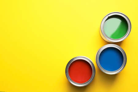 Open paint cans and space for text on color background, top view
