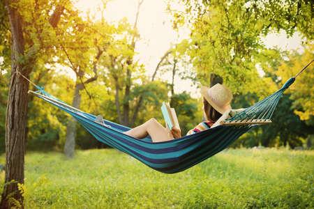 Jonge vrouw leesboek in comfortabele hangmat in groene tuin Stockfoto