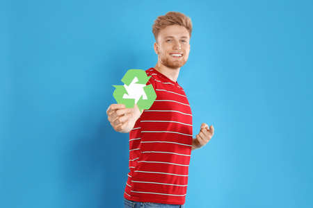 Young man with recycling symbol on blue background 스톡 콘텐츠
