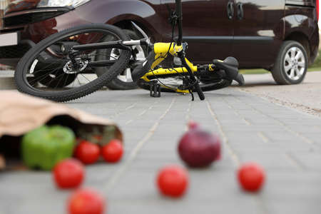 Scattered vegetables and fallen bicycle after car accident on street