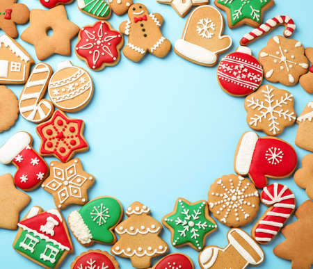 Flat lay composition with tasty homemade Christmas cookies on light blue background, space for text
