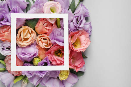 Flat lay composition with beautiful Eustoma flowers on grey background Stock Photo