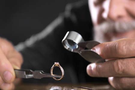 Male jeweler evaluating diamond ring in workshop, closeup view Stok Fotoğraf - 130072847