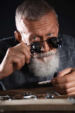 Male jeweler evaluating diamond brooch in workshop