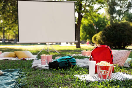 Popcorn and drink on green grass in open air cinema. Space for text