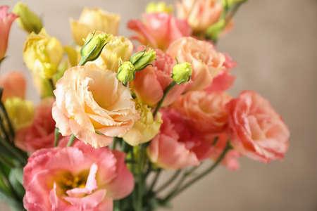 Beautiful Eustoma flowers against beige background, closeup