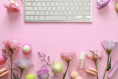 Flat lay composition with keyboard and flowers on pink background. Beauty  workplace