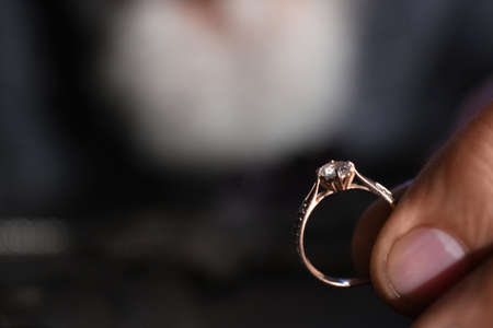 Male jeweler holding diamond ring, closeup view. Space for text