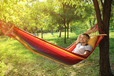 Young man resting in comfortable hammock at green garden