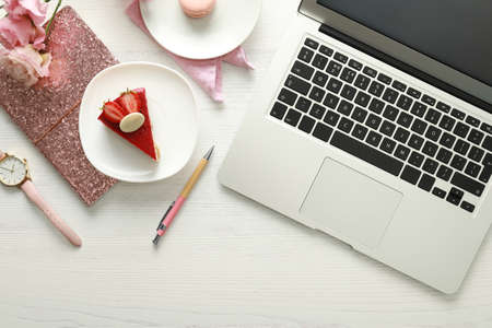 Flat lay composition with laptop on white wooden table.