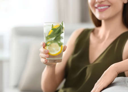 Young woman with lemonade at home, closeup. Refreshing drink