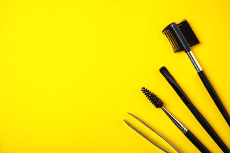 Set of professional eyebrow tools on yellow background, flat lay. Space for text Фото со стока - 130073798