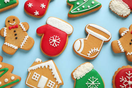 Flat lay composition with tasty homemade Christmas cookies on light blue background